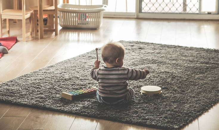Baby playing drums on shag rug