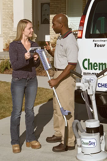 Chem-Dry staff with a female residential client inspecting carpet cleaning equipment